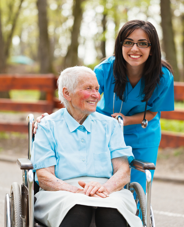 Smiling elderly lady and nurse in park enjoying their time together. photo