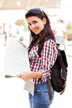 people travelling: Happy tourist with map in her hand, smiling to the camera.