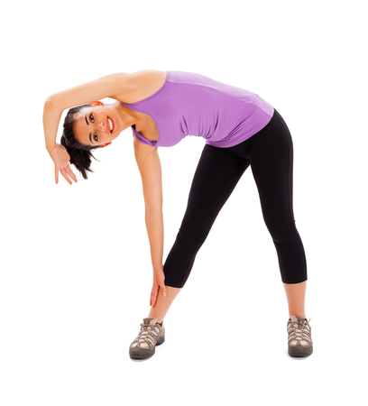 warming up: Beautiful young lady doing her every day fitness workout - isolated background. Stock Photo