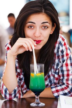 Latina woman drinking cocktail with straw in a bar. photo