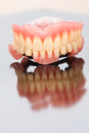 fixate: Dental prosthesis on mirror surface. Stock Photo