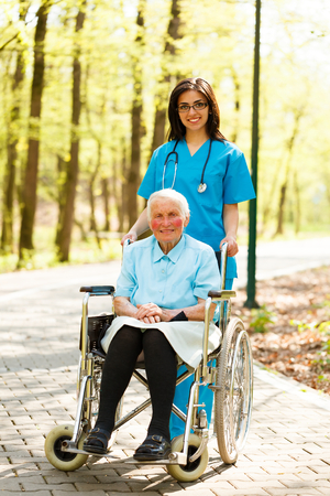 Beautiful nurse and kind elderly lady in wheelchair walking in park together. photo