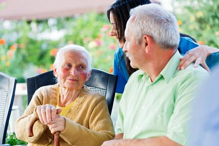 Donna anziana guardando alla badante e suo figlio, il visitatore. Archivio Fotografico - 31324767