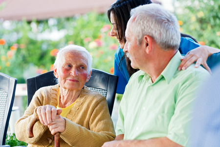 Elderly woman looking to the carer and her son, the visitor.  photo