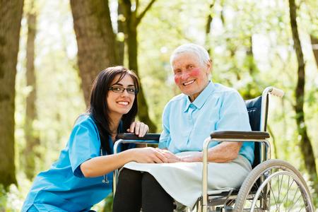 Soort verpleegster die hogere dame patiënt in een rolstoel.