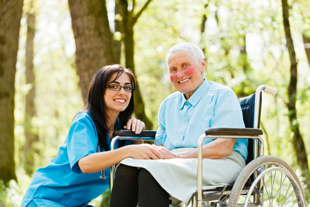 Kind nurse taking care of senior lady patient in wheelchair.