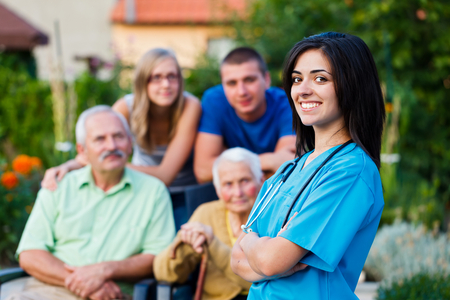 visit: Confident and kind doctor welcoming the family members of the elderly patient. Stock Photo