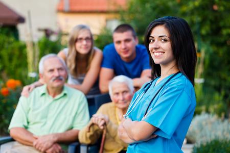 Zuversichtlich und freundlich Arzt Begrüßung der Familienmitglieder der älteren Patienten.