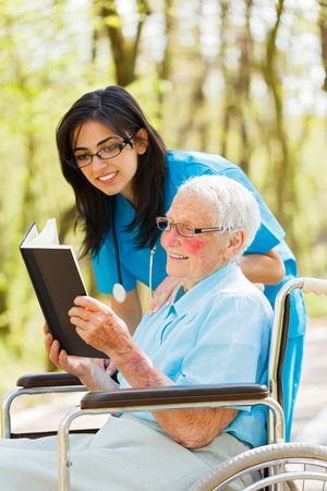 Elderly lady outdoors in wheelchair reading bible with nurse. photo
