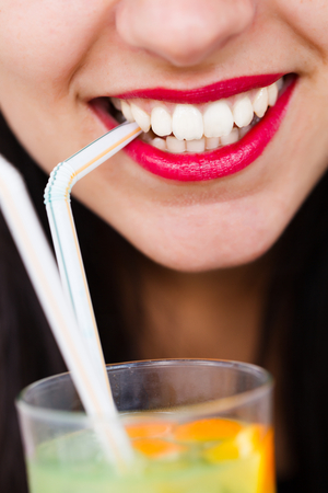 Beautiful woman 's lips with straw and cocktail. photo