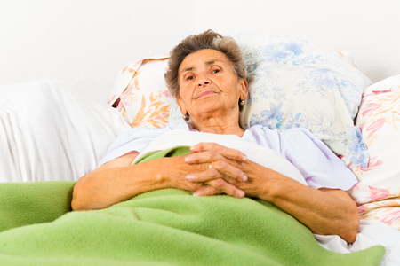 alzheimers: Serene senior woman saying prayers in bed before going to sleep. Stock Photo