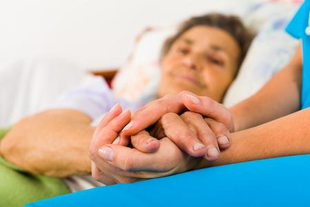 Vårdande sjuksköterska håller slag äldre damens händer i sängen.