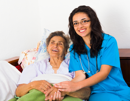 disease patients: Caring nurse having fun with kind elderly patient.