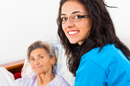 disease patients: Nurses caring for elderly patients suffeing from disease in nursing home.