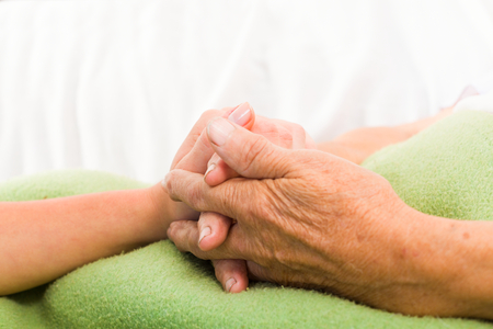 Health care nurse holding elderly ladys hand with caring attitude. photo