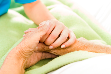 Health care nurse caring for elderly concept - holding hands. photo