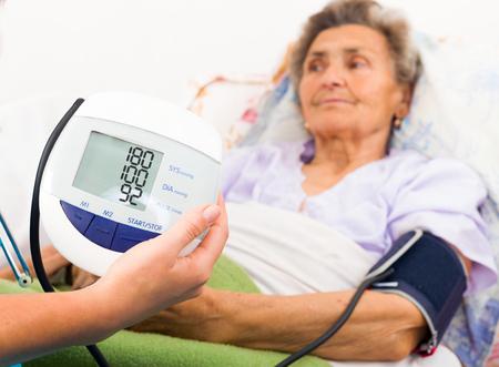 parkinsons: Home care nurse using digital blood pressure measure. Stock Photo