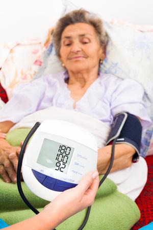 measured: Elderly ladys blood pressure measured by digital gauge. Stock Photo