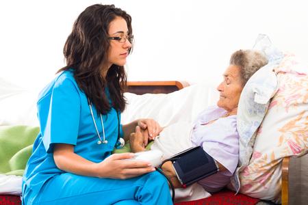 Doctor measuring senior patients blood pressure.