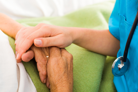 caring: Social care provider holding senior hands in caring attitude - helping elderly people.
