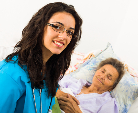 disease patients: Smiling nurse caring for kind elder patient in nursing home.