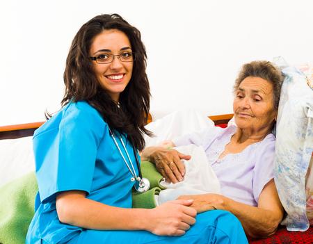 caring for: Smiling nurse caring for kind elder patient in nursing home.
