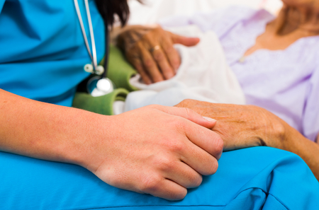 Social care provider holding senior hands in caring attitude - helping elderly people.