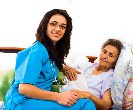 homecare: Happy joyful nurses caring for kind elderly patients helping their days in nursing home. Stock Photo