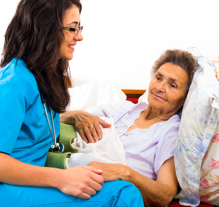 disease patients: Kind nurse easing elderly ladys days in nursing home with care help and joy.