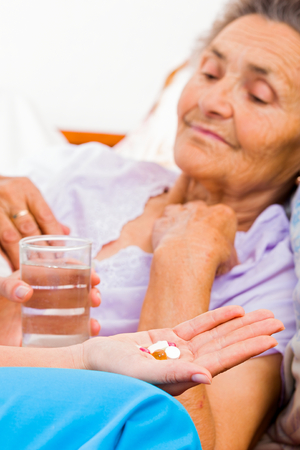 alzheimers: Elderly lady with Alzheimers disease taking pills. Stock Photo