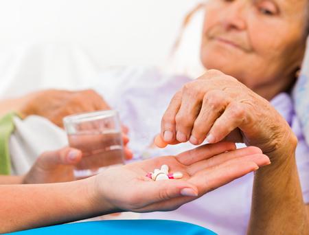 Infirmière de soins à domicile aider dame âgée à prendre ses médicaments tous les jours. Banque d'images - 55422471