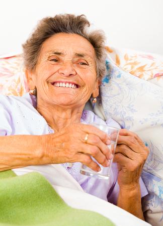 disease patients: Joyful elderly lady taking medication with glass of water.
