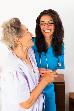 caring for: Nurses caring for elderly patients suffeing from disease in nursing home.