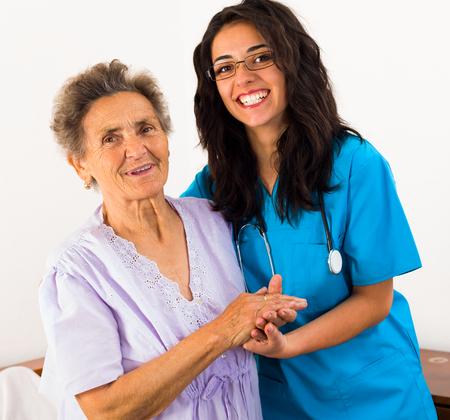 pacientes: Enfermeras alegres felices que atienden a pacientes de edad avanzada en especie para ayudar a sus d�as en la casa de reposo.