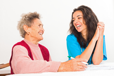 Happy elderly lady laughing with kind nurse carer working in homecare.