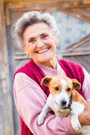 persona de la tercera edad: Mujer mayor de risa con su pequeño cachorro tipo al aire libre. Foto de archivo