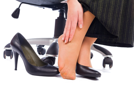 disadvantages: Wearing high heels has its painful disadvantages - hurting feet, ankle. Stock Photo