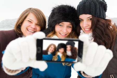 winter photos: Laughing women taking photos with phone camera - winter selfie time.