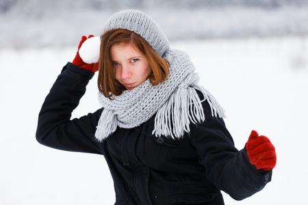 palle di neve: Cutely ragazza pericoloso attaccando con palla di neve in inverno. Archivio Fotografico