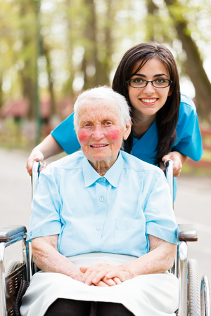 Portrait of an elderly lady and a kind nurse helping her. photo