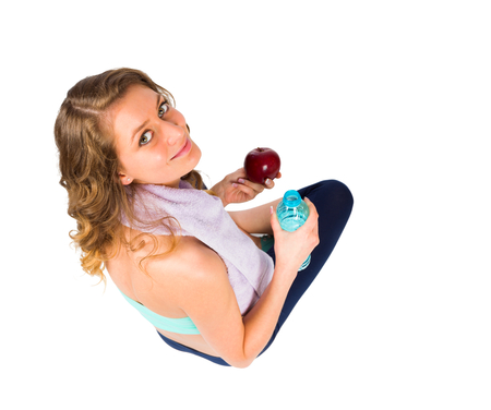 kindly: Amazing girl at gym smiling kindly with towel, water and fruit in hands over white.