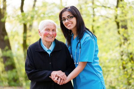 old age home: Portrait of caring nurse helping elderly lady holding her hands.