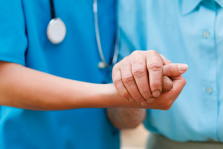 nursing assistant: Doctor holding elderly patients hands with care.