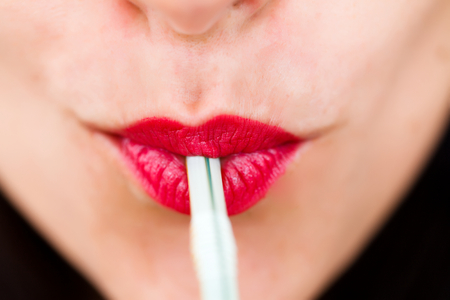 drinking straw: Closeup of female lips consuming a drink with straw.