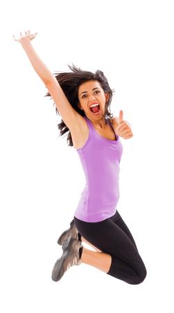 enjoying life: Beautiful fit young lady jumping enjoying her healthy life - studio shot.