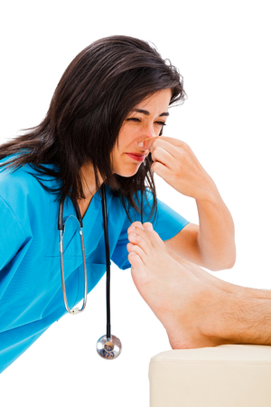 stinky: Female doctor holding her nose above stinky male foot - isolated on white.
