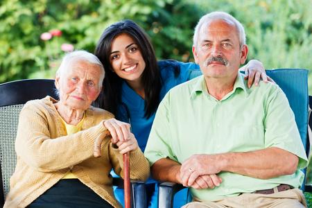 Jonge verpleegkundige of arts met een oudere vrouw en een familielid van haar in de tuin van het verpleeghuis.