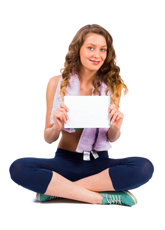 Beautiful young woman on diet with towel holding a blank board. photo