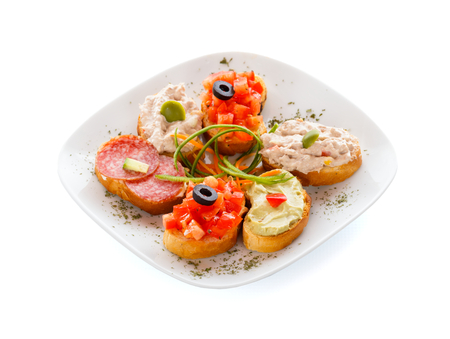 plateful: A plateful of mixed sandwitches: bruschette, guacamole, tuna and salami sandwich. Stock Photo