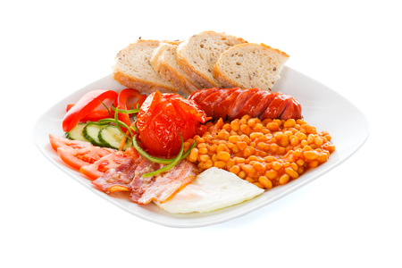 fryed: A creative arranged continental breakfest containing sausages, bean truck, bacon, fresh vegetables, fryed eggs and bread.
